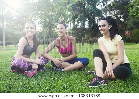 Smiling And Cheerful Friends On Grass In Park After Running