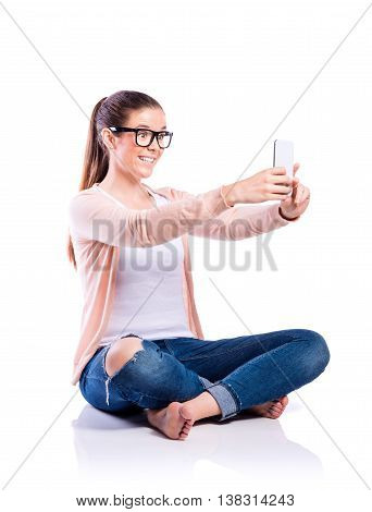 Teenage girl in white t-shirt, pink cardigan, jeans and trendy black eyeglasses, holding a smart phone, taking selfie, sitting on the floor, young beautiful woman, studio shot on white background, isolated