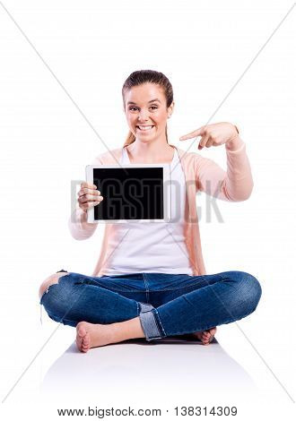 Teenage girl in white t-shirt, pink cardigan and jeans, sitting on the floor, holding tablet, pointing finger on it, young beautiful woman, studio shot on white background, isolated