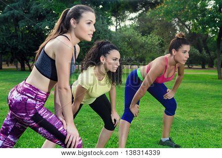 Three Sportswomen Ready To Run In Park