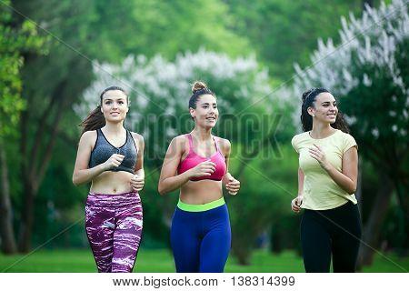 Three Cheerful Sportswomen Running In Park