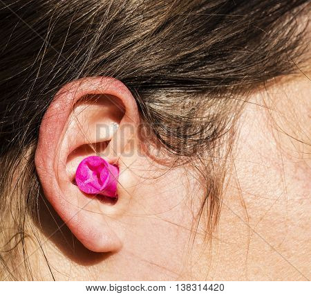 Plugged womans ear for high noise protection.