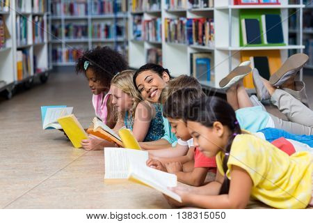 Portrait of smiling teacher with children lying down while reading books in library