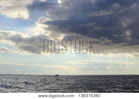 The boat moves quickly toward the shore. approaching rain and storm. heavy clouds