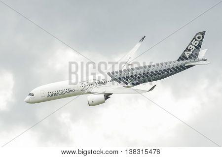 FARNBOROUGH, UK - JULY 13: Airbus A350-941 circling in cloudy skies before landing at Farnborough, Hampshire, UK on July 13, 2016
