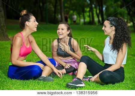 Three Laughing Sportswomen On Grass With Crossed Legs