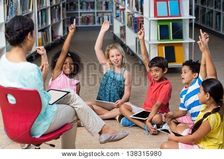 Female teacher sitting on chair by children raising hands in library