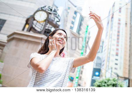 Woman taking selfie by mobile phone in Causeway bay of Hong Kong