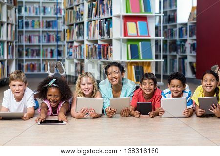 Portrait of smiling teacher with students using digital tablets while lying down in library