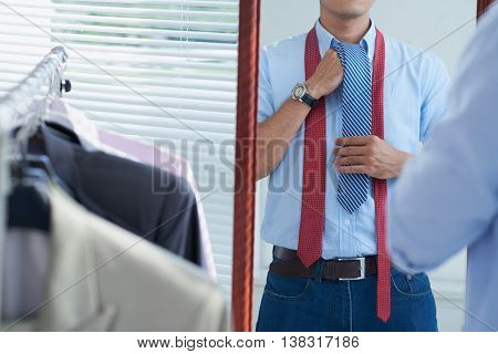 Cropped image of man adjusting tie when getting ready