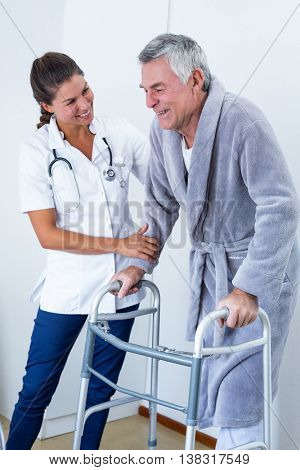 Female doctor helping senior man to walk with walker in hospital