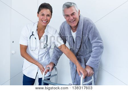 Portrait of female doctor helping senior man to walk with walker in hospital