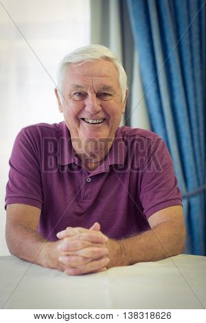 Portrait of smiling senior man sitting in medical clinic