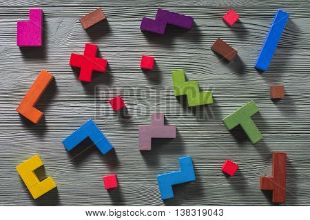 The concept of logical thinking. Geometric shapes on a wooden background, flat lay. Tetris toy wooden blocks.