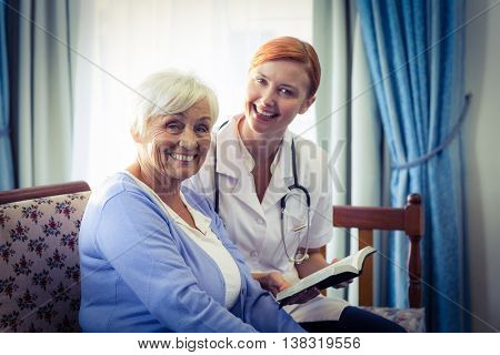 Portrait of smiling doctor helping senior woman to read a book