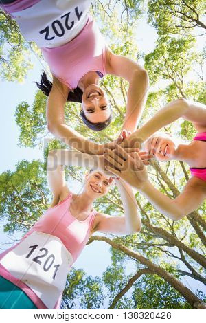 Young athlete women forming hands stack in park
