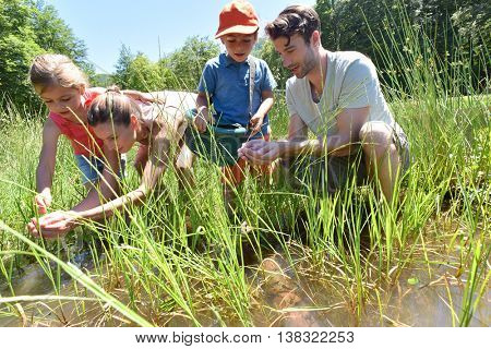 Family in lake looking for tadpoles