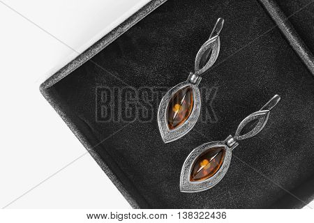 Vintage amber earrings in black jewel box as a background