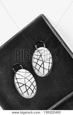 White enameled earrings in black jewel box as a background
