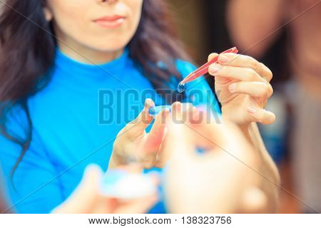 contact lenses in containers and tweezers on blue background