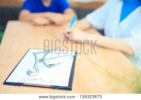 Close-up of stethoscope and paper on background of doctor and patient hands