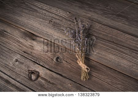 Top view of dried lavender bouquet on grungy wooden background