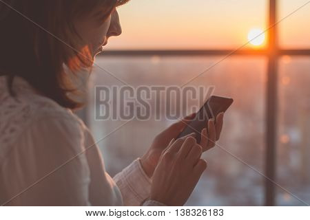 female hands holding smartphone, typing, using touchscreen and wi-fi internet.