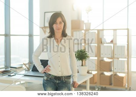 Portrait of woman standing near workplace, looking at camera