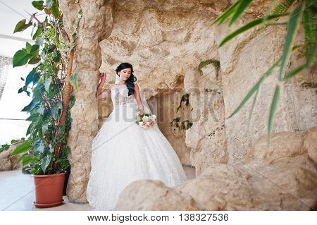 Temptation Model Brunette Bride At Exciting Wedding Dress Posed At Cave Decoration
