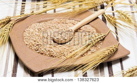 Bamboo plate and wooden spoon filled with wheat bran surrounded by wheat ears on striped cloth napkin, focus on content of the spoon. Dietary supplement to improve digestion. Source of dietary fiber