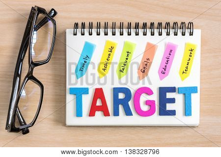 Wood letter of target word with hand writing definition in colorful sticky note on notebook with eye glasses on desk top view