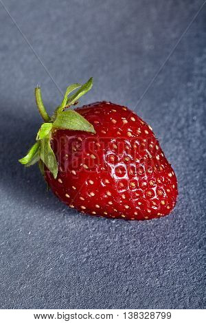 Single fresh and juicy red strawberry with green tail on stone backround.
