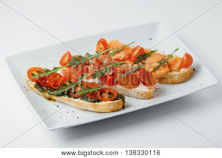 sandwiches with greenary, tomatoes and meat on a white background