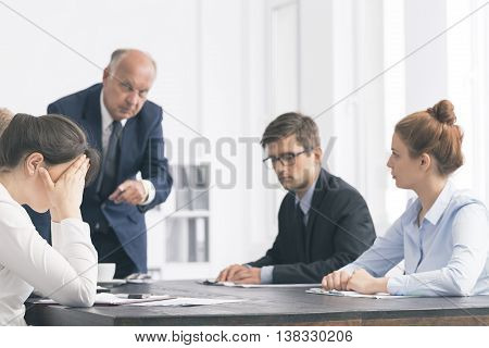 Cropped shot of an angry boss pointing his finger at young businesswoman