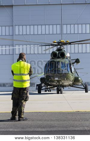 OSTRAVA CZECH REPUBLIC - SEPTEMBER 22: Man in military uniform stands in front of polish Mi-8T helicopter during airshow session NATO Days on September 22 2012 in Ostrava Czech republic.