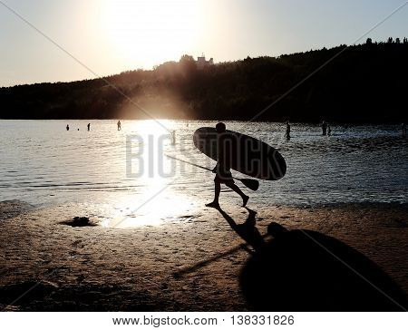 a man carries in his hands a surfboard. Shining bright sun shines and the water. people sunbathe