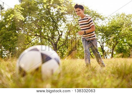 Adolescence and leisure activity. Young kid playing soccer in park running towards the ball smiling happy.