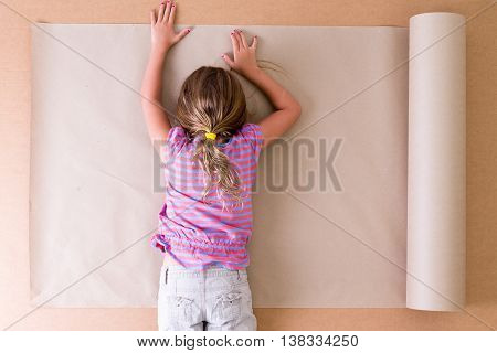 Depressed young little girl artist lying face down on the paper as she struggles to come up with original ideas and creative designs overhead view