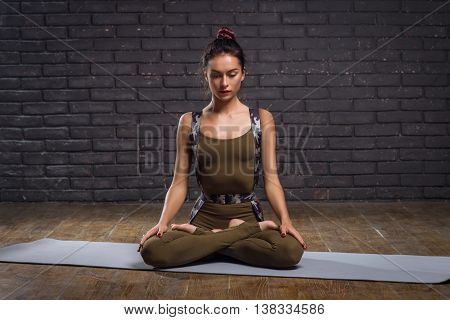 Young Beautiful Woman Practicing Yoga Doing Excercise Against A Brick Wall