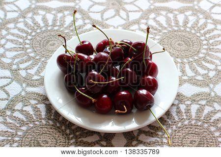 Cherries in white plate on desk. Stock photo.