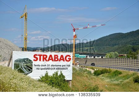 Dolny Hricov, Slovakia - June 29, 2016: Two tower cranes working on construction site of slovak D1 highway billboard of Strabag building company in foreground (translation: