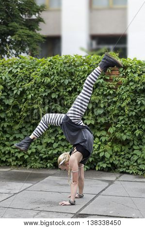 Girl dancing in the city. The choreographic etude on the pavement. Break-dance