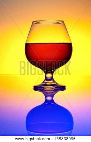 Glass brandy and cognac in color background