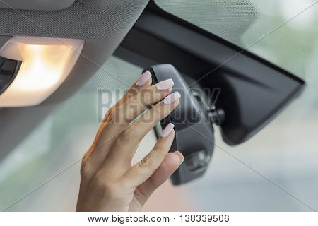 the girl in the car with beautiful manicure adjusts the rearview mirror