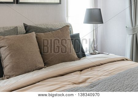 Brown Pillows On Bed With Black Lamp In Modern Bedroom