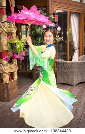 Chinese girl in traditional dress with floral parasol