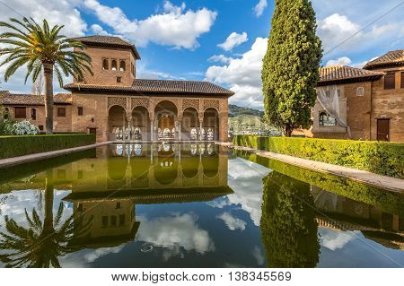 El Partal in Alhambra of Granada, Unesco Heritage Site, Andalusia, Spain. A large central pond faces the arched portico which stands behind the Tower of the Ladies reflecting in the water.