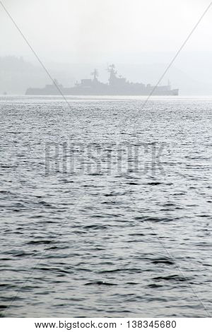 silhouette of a Russian military missile cruiser in the fog