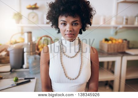 Young African Woman Standing At Juice Bar