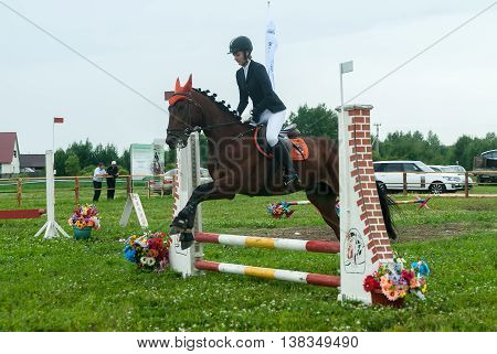 Tyumen, Russia - June 24, 2016: The 5th open championship of Russia on a plowed land. Young girl rider on a horse overcomes obstacles during show program